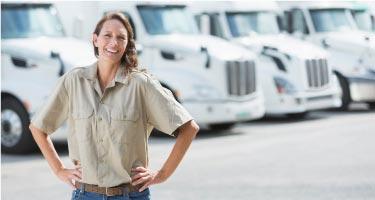 woman in front of fleet of trucks